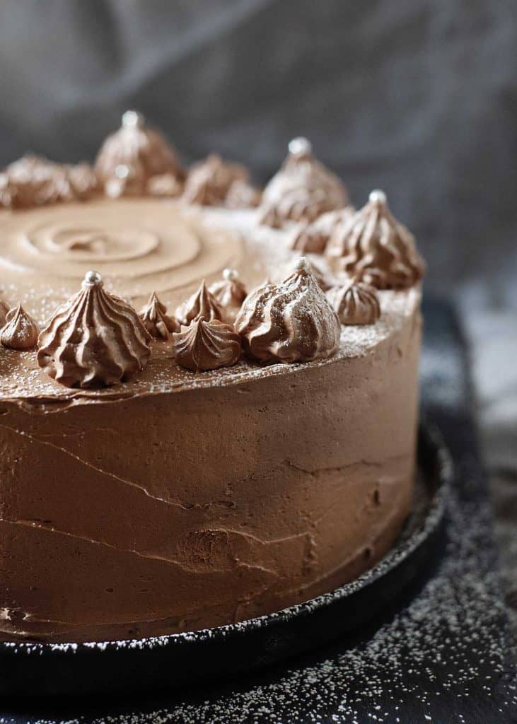 Whole choclate layer cake with chocolate swiss meringue buttercream swirls on top, dusted with powdered sugar against a dark background